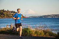 A yong man running on a paved path along the water in Discovery Park, Seattle, Washington, USA.