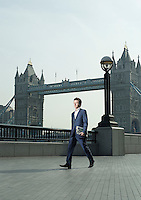 Young business man walking in front of Tower Bridge