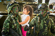 "11 JANUARY 2014 - BANGKOK, THAILAND: A Thai girl looks at Thai special forces soldiers during an Army open house on Children's Day. The Royal Thai Army hosted a ""Children's Day"" event at the 2nd Cavalry King's Guard Division base in Bangkok. Children had an opportunity to look at military weapons, climb around on tanks, artillery pieces and helicopters and look at battlefield medical facilities. The Children's Day fair comes amidst political strife and concerns of a possible coup in Thailand. Earlier in the week, the Thai army announced that movements of armored vehicles through Bangkok were not in preparation of a coup, but were moving equipment into position for Children's Day.      PHOTO BY JACK KURTZ"