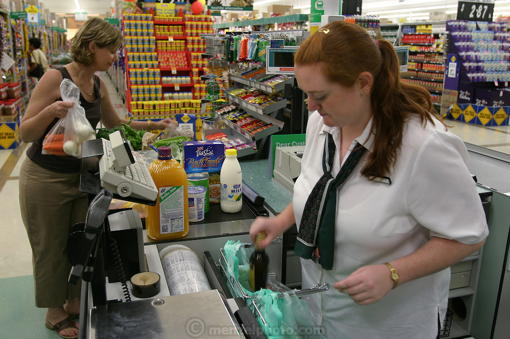 Natalie Molloy at the grocery store checkout counter as she is shopping for her family's upcoming photo shoot. (Supporting image from the project Hungry Planet: What the World Eats.)
