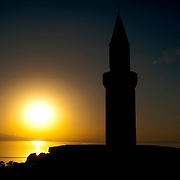 The setting sun casts vivid colors across Van Lake, and silhouettes the minaret of the mosque at Van Castle (Kalesi), Van Province, Eastern Anatolia, Turkey.