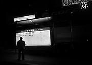 A man checks a bus schedule at night in Chongqing.