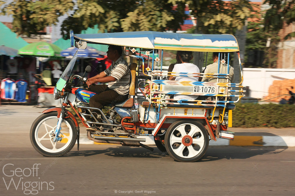 Laotian tricycle motor rickshaw taxi rushes through city streets of Pakse Lao