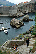 Elevated view of two children (9 years old and 5 years old) ascending steps to Fortress Lovrinjenac (Fort Lawrence), with Dubrovnik's oldest harbour, Kalarinja, Dubrovnik old town and Fortress Bokar in background. Dubrovnik, Croatia