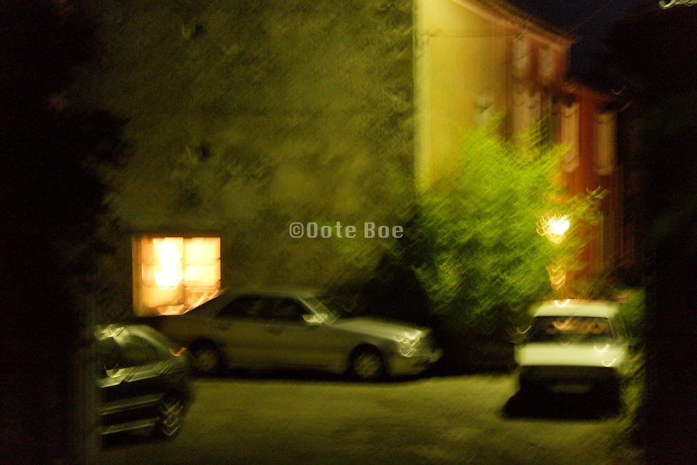 house with parked cars at night, blurry