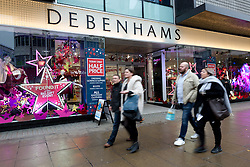 "© Licensed to London News Pictures. 24/11/2015. London, UK. Shoppers walk past a ""Today Only Half Price"" sign displayed in the shop window of Debenhams on Oxford Street. Photo credit : Vickie Flores/LNP"