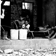 Landmine survivors laying down at the shade of a building under construction in the outskirts of Siem Reap, Cambodia.