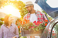 Portrait of mature gardener putting flowers on car trunk while talking to woman in garden shop
