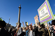 Demonstrators pass Nelson's Column in Trafalgar Square during the Time To Act, National Climate March organised by Campaign Against Climate Change in London, England on March 7, 2015