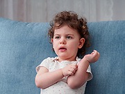 Two year old toddler sits on the couch in a lounge at home