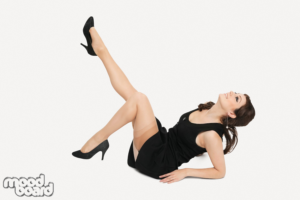 Beautiful young woman in dress sitting on floor with feet up against white background