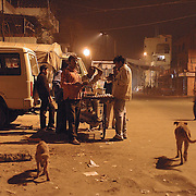 Close to midnight, on a street otherwise busy with heavy traffic, people grab a quick night bite from a passing 'anda-walla' selling eggs and egg sandwiches. .The bun-anda (egg sandwich) vendor selling eggs is one of India's best-known entrepreneurs on whom office goers and night birds depend. New Delhi, India