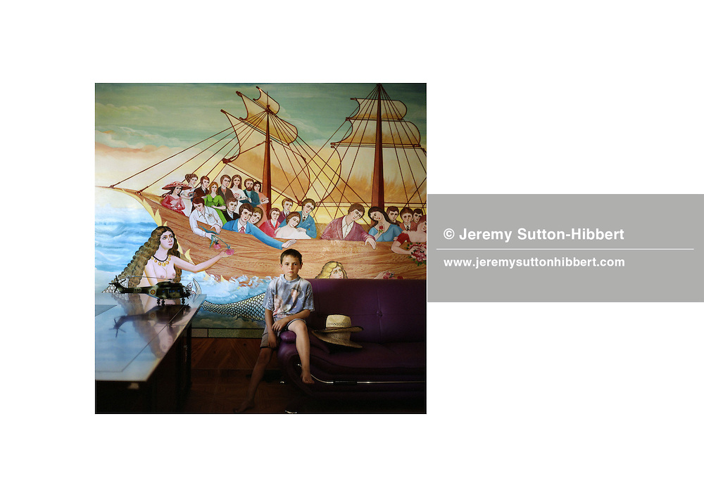 Ionut, a young Roma boy,  sits below a mermaid /nautical painting on the wall of his families home, in the new part of the Sintesti Roma camp. Nautical scenes are very popular as wall decoration, but no-one within the camp knows the reason why they were first painted..