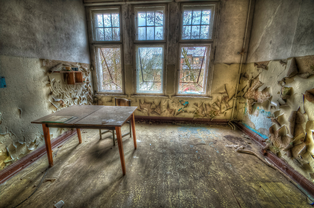 Derelict room interior in old hospital with table