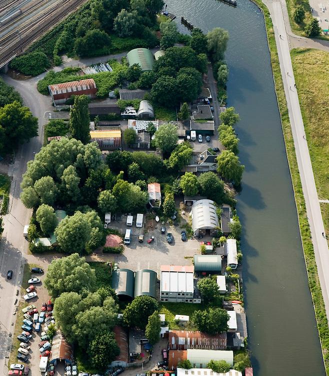 Nederland, Amsterdam, Wenkebachweg, 17-06-2008; terein van de Hells Angels aan de H. J. E. Wenkebachweg, rond een onder het midden van de foto; het nieuw gebouwde clubhuis is het vierkante gebouw met het oranje-witte dak, gelegen aan de bijna lege parkeerplaats; ook de andere gebouwen (nissen loodsen) horen bij 'Angels Place'; rechts het water van de Weesterzijde / Duivendrechtse vaart, linksboven de sporrlijn naar het Amstelsation; rafelrand, neimandsland, motorclub, motoren, motorrijden..luchtfoto (toeslag); aerial photo (additional fee required); .foto Siebe Swart / photo Siebe Swart