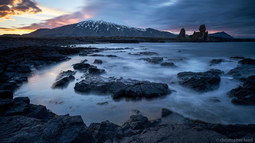Lóndrangar seascape at sunset. Snæfellsjökull glacir in background. Snæfellsnes peninsula, West Iceland.