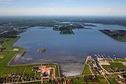Nederland, Groningen, Oldambt, 01-05-2013; boerderijen in Oostwold, aan de oevers van het Oldambtmeer, onderdeel van Blauwestad In de achtergrond). Het meer dienst voor recreatie en waterberging.<br /> Het project Blauwe Stad was oorspronkelijk bedoeld om de economisch achtergebleven regio van Noordoost Groningen een impuls te geven. De economische en huizen crisis gooit echter roet in het eten.<br /> Old farms on the edge of the new recreational Oldambt lake, part of Blauwestad (Blue City), the newly constructed residential area. The Oldambt lake also serves as water storage. The Blue City project is meant to give a boost to the  economically backward region of northeast Groningen, but the financial crisis has slowed down real estate developments.<br /> luchtfoto (toeslag); aerial photo (additional fee required);<br /> foto Siebe Swart / photo Siebe Swart