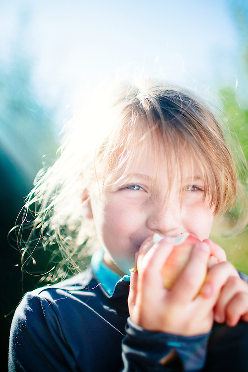 young caucasion girl smiles while eating apple