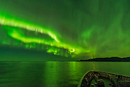 Auroral curtains swirling below the Big Dipper, taken from the coast of Norway on the deck of the Hurtigruten ship m/s Nordlys, October 24, 2017. With the Lights illuminating the sea. <br /> <br /> This is a single 1-second exposure with the Sigma 14mm Art lens at f/1.8 and Nikon D750 at ISO 6400.