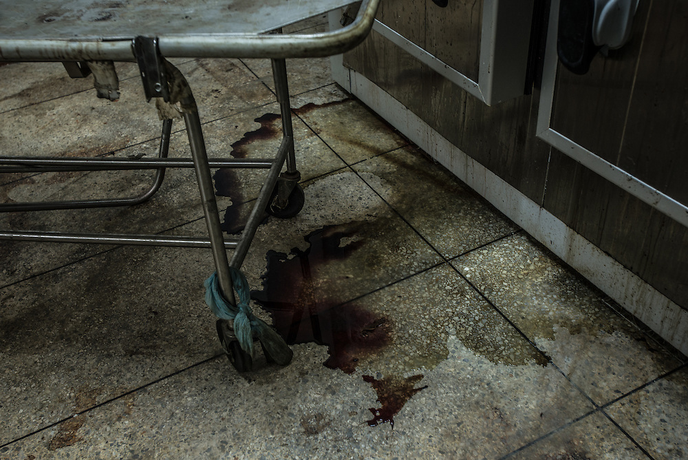 PUERTO LA CRUZ, VENEZUELA - APRIL 15, 2016:  The floors and gurneys are all filthy and stained with dried blood inside the morgue of Hospital Universitario Dr. Luís Razetti - one of the worst state-run, public hospitals in Venezuela.  Doctors compare it to working in a war zone - they regularly have to turn patients away, because they don't have the majority of medicines  or medical equipment and supplies needed to give them medical attention.  When they do accept patients, they have to work with extremely limited resources, because they don't have the supplies they need for things like X-Rays,  and many exams nd operations.  The hospital's infrastructure is crumbling, and staff don't have all the cleaning supplies required to keep the hospital sanitary. The hospital also suffers from weekly shortages of running water and electricity.  In April, several babies died when a power outage turned off the incubators, and the hospital's generator failed to work because of lack of maintenance.  The same month, authorities found over 100 pieces of medical equipment, stolen from the hospital in the home of the assistant to the hospital's director.  Despite having the largest oil reserves in the world, falling oil prices and wide-spread government corruption have pushed Venezuela into an economic crisis, with the highest inflation in the world and chronic shortages of food and medical supplies.  PHOTO: Meridith Kohut for The New York Times