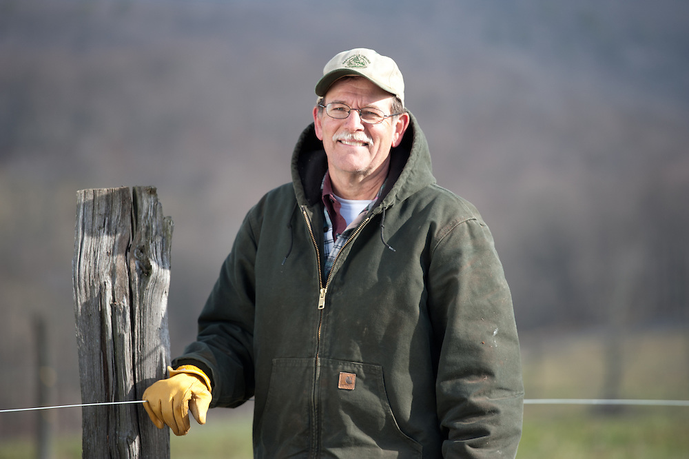Farmer stands smiling against fence.