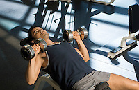 Man using dumbbells in gymnasium