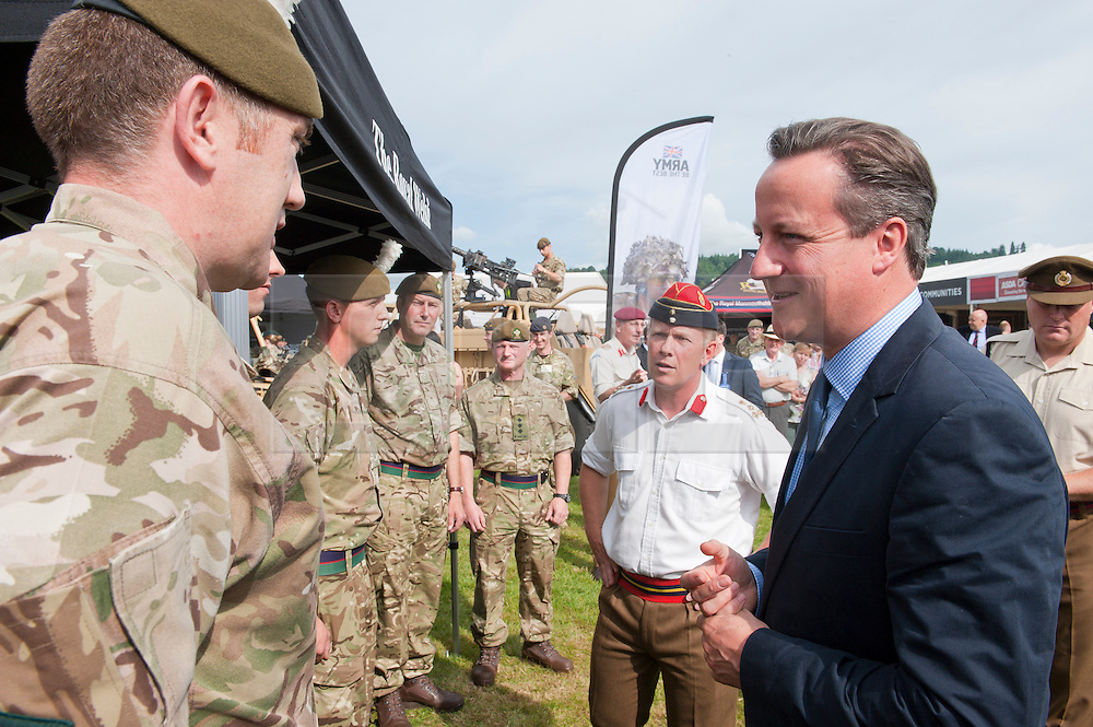© Licensed to London News Pictures. 21/07/2014. Llanelwedd, UK. David Cameron visits the military stand at the show. A record numbers of visitors in excess of 240,000 are expected this week over the four day period of Europe's largest agricultural show. Livestock classes and special awards have attracted 8,000 plus entries, 670 more than last year. The first ever Royal Welsh Show was at Aberystwyth in 1904 and attracted 442 livestock entries. Photo credit: Graham M. Lawrence/LNP