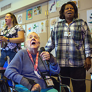 MANASSAS, VA - NOV21:  Norma Felter does karaoke with activity aide Tina Burhans-Robinson (left) and Thelma Wallace (right), a quality care aid, at Birmingham Green, an elder care residence in Manassas, VA, November 21, 2014. With the U.S. population aging and Alzheimer's more widespread, science is looking for ways to slow or delay the onset of dementia in aging Americans. Among the approaches is trying to determine whether art, music and dance or movement can also alleviate the problems attendant with dementia. The federal government is funding a study at Birmingham Green with George Mason University to see whether there is a scientific basis to believe that art is actually medically beneficial. (Photo by Evelyn Hockstein/For The Washington Post)