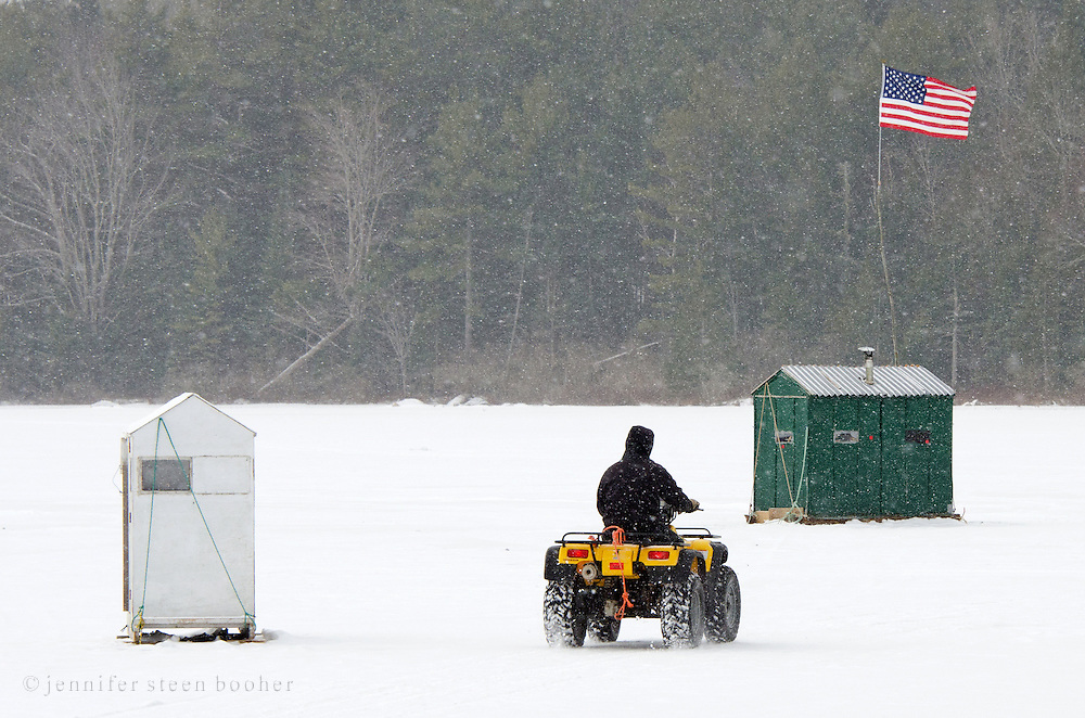 A man drives an ATV between ice fishing huts on a frozen lake during a blizzard.