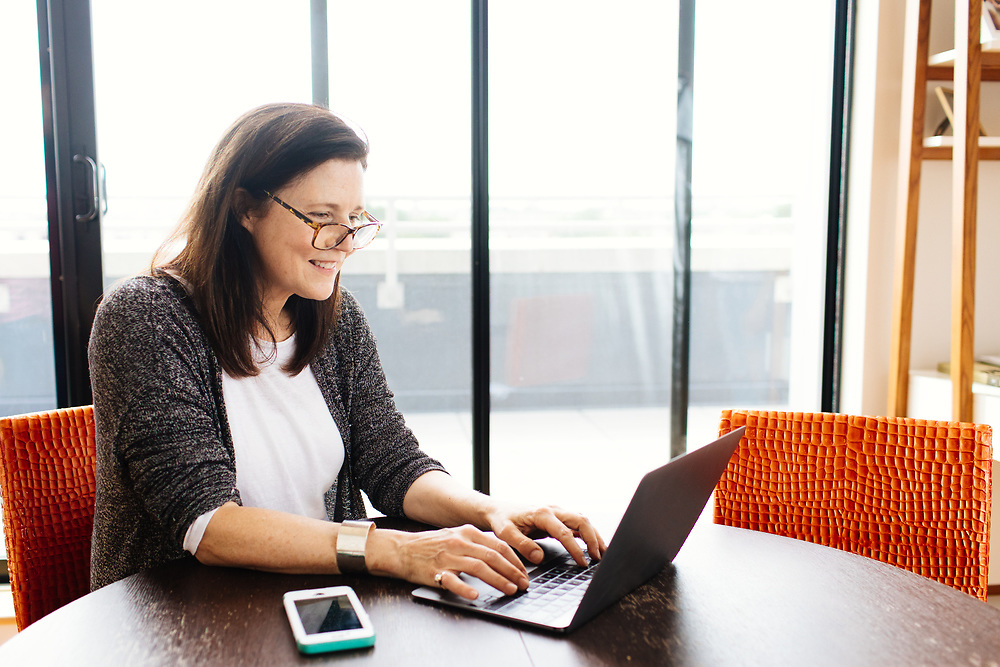 Mature woman working from home at a paperless table