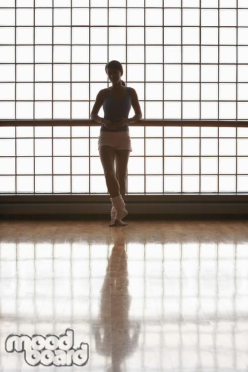Ballerina in stood by window