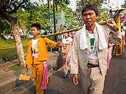 "05 APRIL 2015 - CHIANG MAI, CHIANG MAI, THAILAND: Men carry a gong that announces the arrival of a parade of Buddhist novices in Chiang Mai during the second day of the three day long Poi Song Long Festival in Chiang Mai. The Poi Sang Long Festival (also called Poy Sang Long) is an ordination ceremony for Tai (also and commonly called Shan, though they prefer Tai) boys in the Shan State of Myanmar (Burma) and in Shan communities in western Thailand. Most Tai boys go into the monastery as novice monks at some point between the ages of seven and fourteen. This year seven boys were ordained at the Poi Sang Long ceremony at Wat Pa Pao in Chiang Mai. Poy Song Long is Tai (Shan) for ""Festival of the Jewel (or Crystal) Sons.    PHOTO BY JACK KURTZ"
