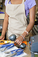 Mid section of female store clerk scanning product with barcode scanner