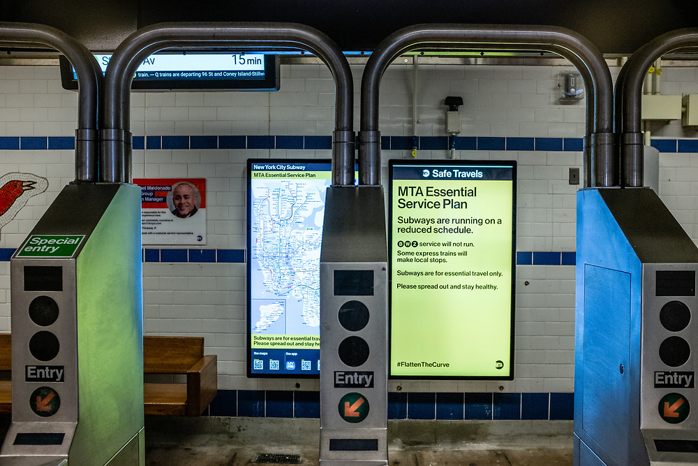 Brooklyn, NY. 5 April 2020. Signs in the entrance to the Avenue J station on the subway's Q line announce service restrictions, and ask that all non-essential riders stay home. This sign notes some a reduced schedule.