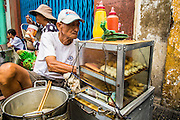 "12 APRIL 2012 - HO CHI MINH CITY, VIETNAM:  A grilled meat vendor on a street in Cholon, the Chinese-influenced section of Ho Chi Minh City (former Saigon). It is the largest ""Chinatown"" in Vietnam. Cholon consists of the western half of District 5 as well as several adjoining neighborhoods in District 6. The Vietnamese name Cholon literally means ""big"" (lon) ""market"" (cho). Incorporated in 1879 as a city 11 km from central Saigon. By the 1930s, it had expanded to the city limit of Saigon. On April 27, 1931, French colonial authorities merged the two cities to form Saigon-Cholon. In 1956, ""Cholon"" was dropped from the name and the city became known as Saigon. During the Vietnam War (called the American War by the Vietnamese), soldiers and deserters from the United States Army maintained a thriving black market in Cholon, trading in various American and especially U.S Army-issue items.        PHOTO BY JACK KURTZ"
