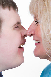 Portrait of a mother and teenage son with Downs Syndrome touching noses,