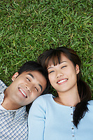 Mid adult couple lying on grass portrait elevated view
