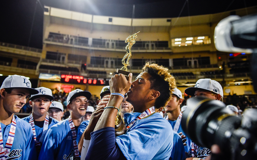 rer051317b/sports/May 13, 2017/Albuquerque Journal<br /> La Cueva's Jonathan Stroman(Cq),center, kisses the 6A trophy after defeating Cleveland for the State tile Saturday evening at Isotopes Park. <br /> Roberto E. Rosales/Albuquerque Journal Photo by Roberto E. Rosales