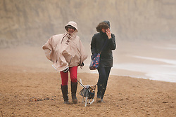 © Licensed to London News Pictures. 03/03/2019. West Bay, UK. Visitors to West Bay in Dorset walk on the beach as storm Freya whips up the waves. Photo credit: Jason Bryant/LNP