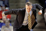 Tulsa head basketball coach Doug Wojcik punches the air in anger after a foul call during their game against UCF in Tulsa, OK.
