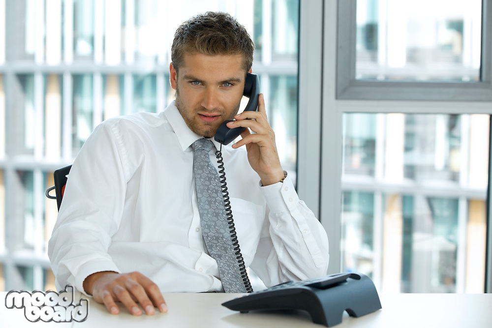 portrait of young confident caucasian businessman talking on phone