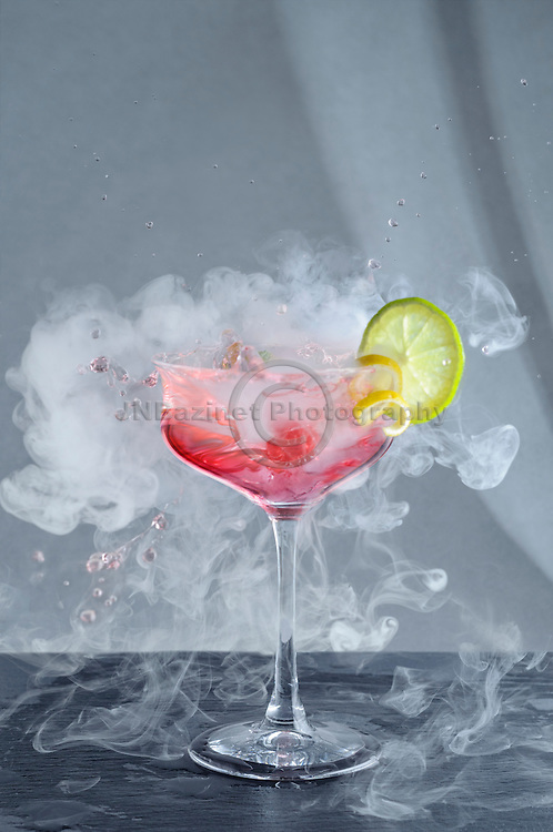 Vibrant pink, splashing, smoky craft cocktail with fruit