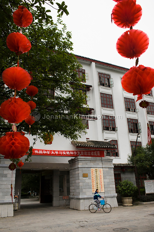 Red paper decorations celebrating Chinese National Day hang from trees outside a government building in Yangshuo, China.