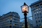 A period lamp and evening lights in modern offices in the City of London - the capital's financial district, on 9th November 2018, in London England.