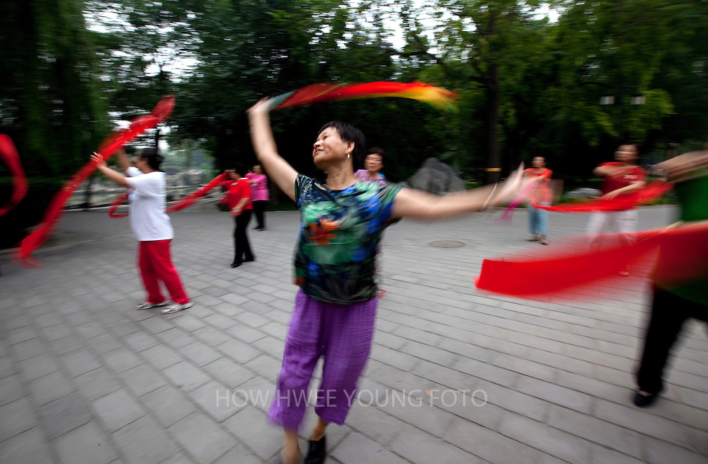 epa02320511 Chinese residents dancing with ribbons in a park in Beijing, China on 07 September 2010. Chinese people generally are living longer, healthier lives with average life expectancy rising to 71 years. However, national averages mask regional disparities, with higher mortality rates prevalent in poor rural regions, especially Western China.  EPA/HOW HWEE YOUNG