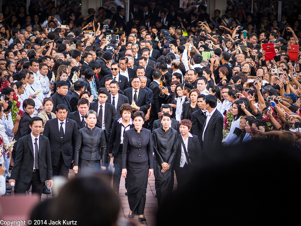 19 OCTOBER 2014 - BANG BUA THONG, NONTHABURI, THAILAND: YINGLUCK SHINAWATRA, former Prime Minister of Thailand, (center) leads family and mourners into Apiwan Wiriyachai's cremation at Wat Bang Phai in Bang Bua Thong, a Bangkok suburb, Sunday. Apiwan was a prominent Red Shirt leader. He was member of the Pheu Thai Party of former Prime Minister Yingluck Shinawatra, and a member of the Thai parliament and served as Yingluck's Deputy Prime Minister. The military government that deposed the elected government in May, 2014, charged Apiwan with Lese Majeste for allegedly insulting the Thai Monarchy. Rather than face the charges, Apiwan fled Thailand to the Philippines. He died of a lung infection in the Philippines on Oct. 6. The military government gave his family permission to bring him back to Thailand for the funeral. His cremation was the largest Red Shirt gathering since the coup.     PHOTO BY JACK KURTZ