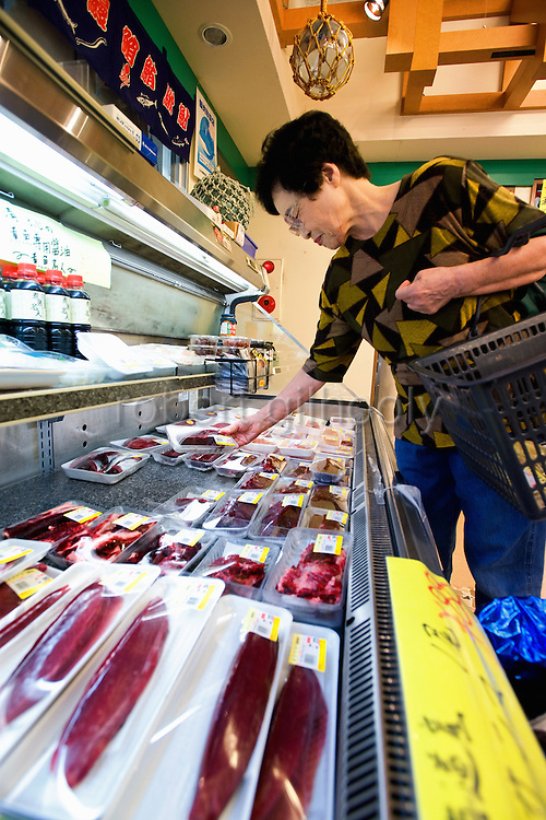 A woman looks at freshly caught and packaged dolphin meat and other sashimi products at a supermarket in Taiji, Japan on 10 September 2009. A small 250 gram block of short fin dolphin meat was selling for around 1,200 yen (US$13.20), though reports a week or so after this photo was taken said the meat had been removed from the supermarket shelves and subsequently was only available to locals from a undisclosed warehouse..Photographer: Robert Gilhooly