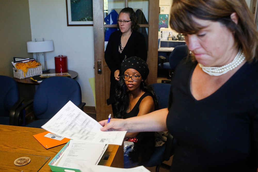 Senior Alexis Lowe looks on as counselor Danielle Ralston, foreground, walks back to her desk after printing off Lowe's official transcript Thursday, May 19, 2016, at City High Middle School, in Grand Rapids, Mich. Lowe plans to attend Texas Southern in the fall.