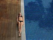 Young Woman in Bikini Lying by Swimming Pool