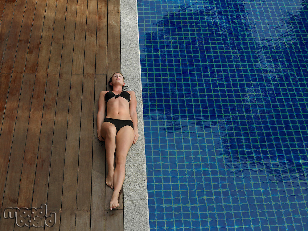 Young Woman in Bikini Lying by Swimming Pool